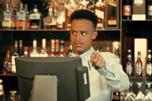 serveur d'un restaurant qui manipule une caisse enregistreuse tactile